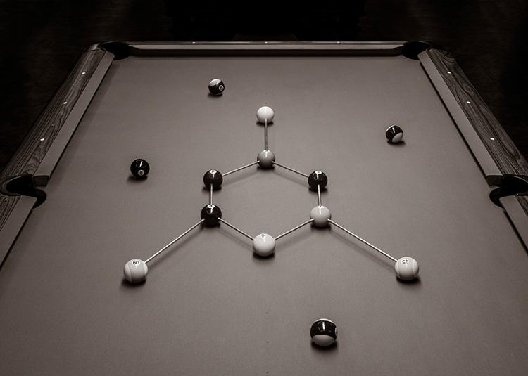 Mesa de billar con bolas representándo una molécula